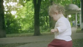 Little blonde baby girl walks in the park on a summer day royalty free stock photo