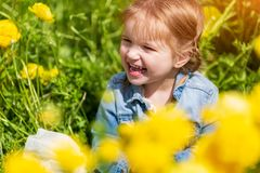 Little blonde Baby between yellow flowers smiling and looking away royalty free stock photos