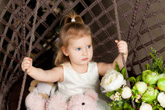 The little blonde blue-eyed girl sitting on a swing knit. Cute girl in white dress on the swing with a Teddy bear in his hands. In the frame of beautiful flowers Stock Photos