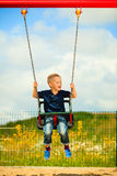 Little blonde boy child having fun on a swing outdoor Royalty Free Stock Image
