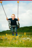 Little blonde boy child having fun on a swing outdoor Stock Image