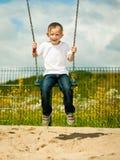Little blonde boy child having fun on a swing outdoor Stock Image