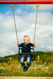 Little blonde boy child having fun on a swing outdoor Stock Photos