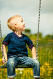 Little blonde boy child having fun on a swing outdoor Stock Images
