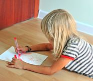 Little blonde boy drawing on floor royalty free stock photos