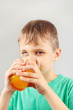 Little blonde boy drinking fresh citrus juice Stock Image