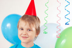 Little blonde boy in festive cap with holiday balls and streamer Stock Photography