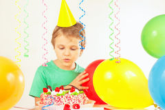 Little blonde boy in festive cap looking at birthday cake Stock Photography