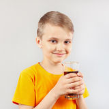 Little blonde boy with glass of fresh cola Royalty Free Stock Photos