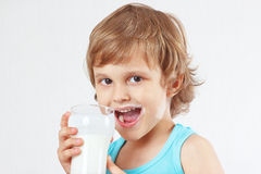 Little blonde boy with glass of a fresh kefir on white background Royalty Free Stock Photo