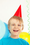 Little blonde boy in holiday cap with festive balls and streamer Royalty Free Stock Photo