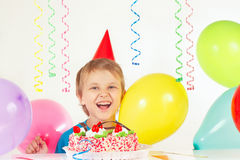 Little blonde boy in holiday hat with birthday cake and balloons Stock Photography