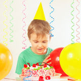 Little blonde boy in a holiday hat looking at the birthday cake Royalty Free Stock Photo