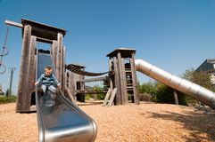 Little blonde boy playing on the slide. Little blonde boy playing on the metal slide on a sunny day in the park Stock Images