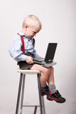 Little blonde boy sits on chair with portable dvd player. Young child watch movie, sitting on a high seat stock images