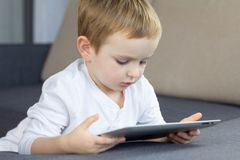 Little blonde boy using touchscreen tablet at home. Happy smart child watching tutorials or playing game on tablet computer. royalty free stock photography