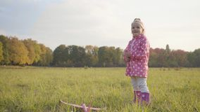 Little blonde caucasian girl dressed in dotted pink jacket and rubber boots playing with a toy airplane outdoors. Cute. Child running in the autumn park in the stock video
