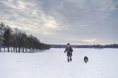Little blonde caucasian Swedish girl running and playing with dog in winter landscape Stock Photography