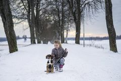 Little blonde caucasian Swedish girl sitting with dog at road in winter alley Royalty Free Stock Image