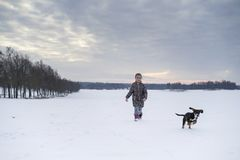 Little blonde caucasian Swedish girl walking and playing with dog in winter landscape Royalty Free Stock Image