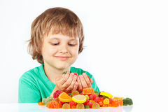 Little blonde child with colored jelly candies on white background stock images
