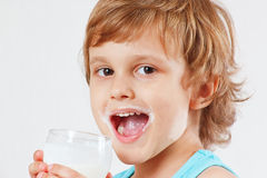 Little blonde child drinking fresh milk on white background Royalty Free Stock Image