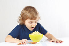 Little blonde child is going to breakfast a millet porridge Royalty Free Stock Photos
