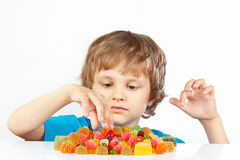 Little blonde child with jelly candies on white background royalty free stock images