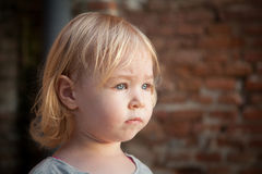 Little blonde child with worried expression near brickwall Stock Photography