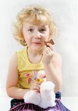Little blonde curly girl eating chocolate. Little blonde curly girl with chocolate Royalty Free Stock Image