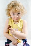 Little blonde curly girl eating chocolate. With toys Royalty Free Stock Image
