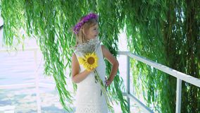 Little blonde with flower`s crown and flowers in hands smiles at camera 4K.  stock footage