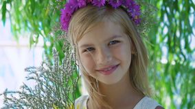 Little blonde with flower`s crown and flowers in hands smiles at camera 4K.  stock video footage