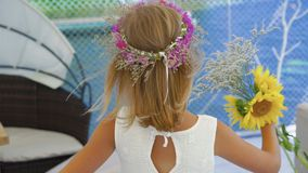 Little blonde with flower`s crown and flowers in hands spinning on the beach 4K.  stock video