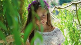 Little blonde with flower`s crown smiling at camera throught the tree branches. Little blonde with flower`s crown on the head smiling at camera throught the tree stock footage