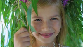 Little blonde with flower`s crown posing at camera through tree branches 4K.  stock video