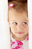 Little blonde girl. Look out of the door close-up Stock Photo