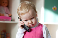 The little blonde girl. Talking on the phone Royalty Free Stock Image