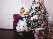 Little blonde girl in beautiful dress decorating Christmas tree at home Royalty Free Stock Photo