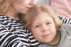 Little blonde girl. Being hugged by her mom Stock Photo