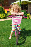 Little blonde girl with bicycle Stock Photography
