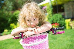 Little blonde girl with bicycle Stock Image