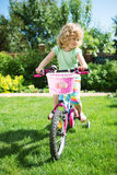 Little blonde girl with bicycle Stock Images
