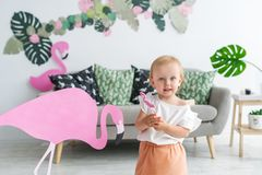 Little blonde girl in big hat standing in her room. Small girl and pink flamingo indoors.  stock images