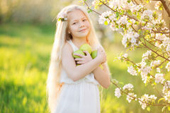 Little blonde girl in blossom garden with apples Stock Photography