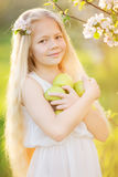 Little blonde girl in blossom garden with apples Stock Image