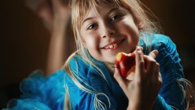 A little blonde girl in a blue blouse lies in a dark room and eats an apple. The girl is holding a biting apple.  Royalty Free Stock Images