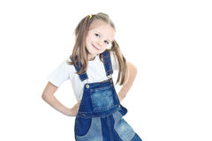 Little blonde girl in blue overalls Stock Images