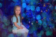 Little blonde girl  in blue and white dress. Little blonde girl at the Christmas tree in blue and white dress Royalty Free Stock Image