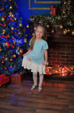 Little blonde girl  in blue and white dress. Little blonde girl at the Christmas tree in blue and white dress Stock Photo